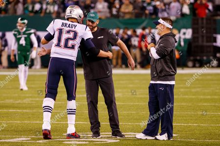 Stock Image of , 2019, New York Jets head coach Adam Gase gives New England Patriots quarterback Tom Brady (12) a hug as he was talking with offensive coordinator Josh McDaniels prior to the NFL game between the New England Patriots and the New York Jets at MetLife Stadium in East Rutherford, New Jersey