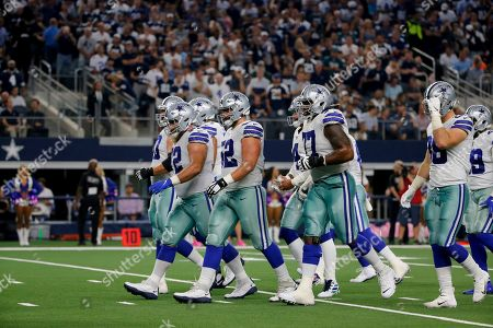 Travis Frederick, Connor Williams, Tyron Smith. Dallas Cowboys' Travis Frederick (72), Connor Williams (52), Tyron Smith (77) and the rest of the line approach the line of scrimmage during an NFL football game against the Philadelphia Eagles in Arlington, Texas