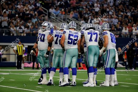Zack Martin, Travis Frederick, Connor Williams, Tyron Smith, Jason Witten. Dallas Cowboys' Zack Martin (70), Travis Frederick (72), Connor Williams (52), Tyron Smith (77), Jason Witten (82) and others huddle on the field during an NFL football game against the Philadelphia Eagles in Arlington, Texas