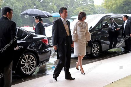 Japan's Prime Minister Shinzo Abe, left, and his wife Akie arrive at the Imperial Palace to attend the proclamation ceremony of Japan's Emperor Naruhito in Tokyo