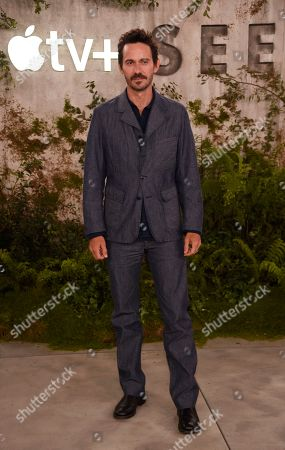 """Stock Picture of Christian Camargo, a cast member in the Apple TV+ series """"See,"""" poses at the premiere at the Regency Village Theatre, in Los Angeles"""