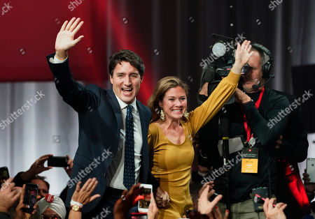 Liberal leader Justin Trudeau and wife Sophie Gregoire Trudeau wave as they go on stage at Liberal election headquarters in Montreal