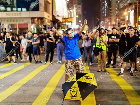 A protester stands off with police. Police fire tear gas to disperse anti-government protesters in Yuen Long.