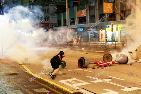 A protester pouring water to extinguish a tear gas canister. Police fire tear gas to disperse anti-government protesters in Yuen Long.