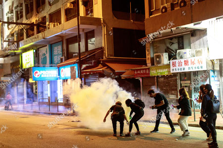 Protesters pour water to extinguish a tear gas canister. Police fire tear gas to disperse anti-government protesters in Yuen Long.