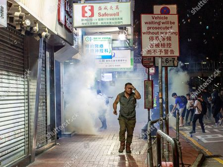 A man runs from tear gas. Police fire tear gas to disperse anti-government protesters in Yuen Long.