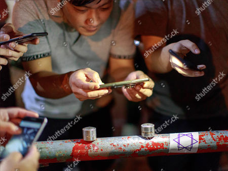 Bystanders take picture of fired tear gas canisters believed made in China. Police fire tear gas to disperse anti-government protesters in Yuen Long.
