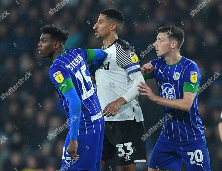 Curtis Davies of Derby County is marked by Dujon Sterling and Joe Williams of Wigan Athletic