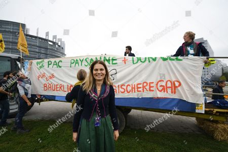 Stock Image of Austrian Green MP and television cook Sarah Wiener stands in front of a banner during a demonstration for a sustainable EU agricultural reform in front of the European Parliament in Strasbourg, France, 22 October 2019. They demanded that EU agricultural subsidies be paid only to farmers who protect the environment and the climate and keep animals in an appropriate manner.