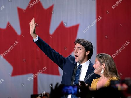 Stock Image of Liberal leader Justin Trudeau and wife Sophie Gregoire Trudeau wave as they go on stage at Liberal election headquarters in Montreal