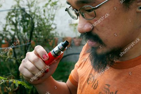 Stock Image of Scott Bloom of Minneapolis, vapes with an electronic cigarette while posing outside his home. Bloom talked about his switch to vaping after experiencing allergies from cigarette smoke