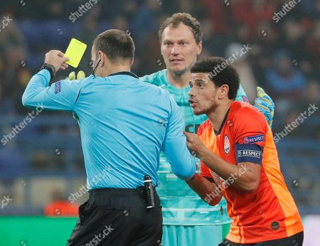 Stock Photo of Andriy Pyatov (C) goalkeeper  and Taison (R) player of Shakhtar argue with referee before penalty during the UEFA Champions League group C soccer match between FC Shakhtar Donetsk and GNK Dinamo Zagreb in Kharkiv, Ukraine, 22 October 2019.