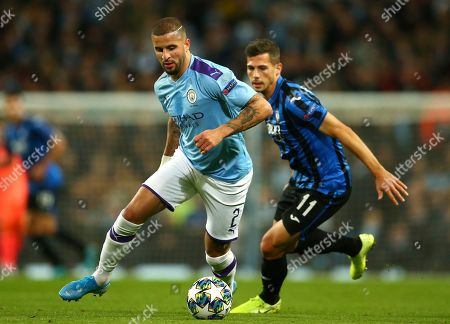 Manchester City's Kyle Walker, left, challenges for the ball with Atalanta's Remo Freuler during the group C Champions League soccer match between Manchester City and Atalanta at the Etihad Stadium in Manchester, England