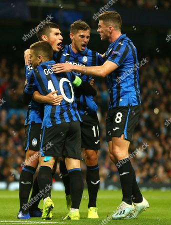 Atalanta's Ruslan Malinovskyi, left, celebrates with his teammates Papu Gomez, Remo Freuler and Robin Gosens after scoring on a penalty kick his side's first goal, during the group C Champions League soccer match between Manchester City and Atalanta at the Etihad Stadium in Manchester, England