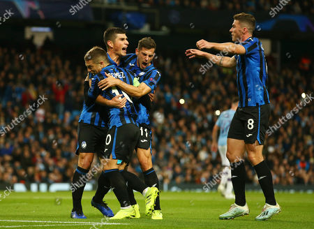 Atalanta's Ruslan Malinovskyi, second from left, celebrates with his teammates Papu Gomez, left, Remo Freuler and Robin Gosens after scoring on a penalty kick his side's first goal, during the group C Champions League soccer match between Manchester City and Atalanta at the Etihad Stadium in Manchester, England