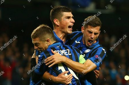 Atalanta's Ruslan Malinovskyi, center, celebrates with his teammates Papu Gomez, left, Remo Freuler after scoring on a penalty kick his side's first goal, during the group C Champions League soccer match between Manchester City and Atalanta at the Etihad Stadium in Manchester, England