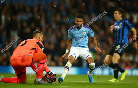 Atalanta's goalkeeper Pierluigi Gollini saves on an attempt to score by Manchester City's Benjamin Mendy during the group C Champions League soccer match between Manchester City and Atalanta at the Etihad Stadium in Manchester, England