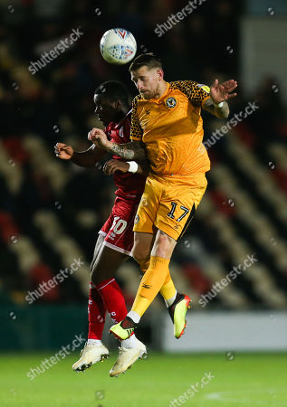 Scot Bennett of Newport County heads the ball forward as Bez Lubala of Crawley Town challenges