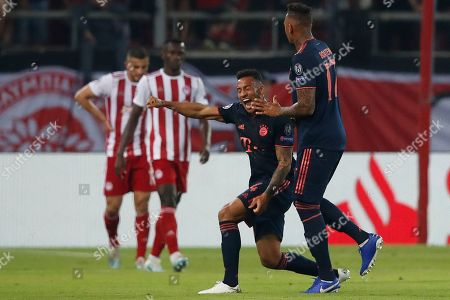 Bayern's Corentin Tolisso, center, celebrates with team mate Bayern's Jerome Boateng after scoring his side's third goal during the Champions League group B soccer match between Olympiakos and Bayern Munich at the Georgios Karaiskakis stadium, in Piraeus port, near Athens