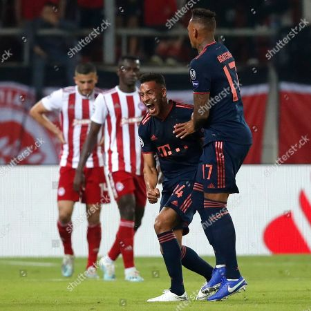 Bayern's Corentin Tolisso, center, celebrates with team mate Jerome Boateng after scoring his side's third goal during the Champions League group B soccer match between Olympiakos and Bayern Munich at the Georgios Karaiskakis stadium, in Piraeus port, near Athens
