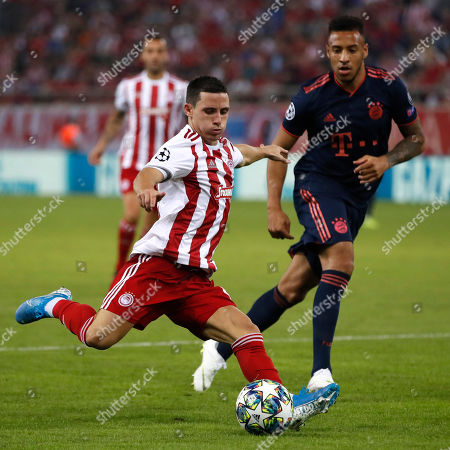 Olympiakos' Daniel Podence, foreground, kicks the ball in front of Bayern's Corentin Tolisso during the Champions League group B soccer match between Olympiakos and Bayern Munich at the Georgios Karaiskakis stadium, in Piraeus port, near Athens
