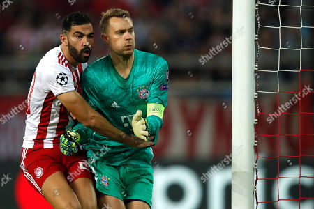 Olympiakos' Yassine Meriah, left, blocks Bayern's goalkeeper Manuel Neuer during the Champions League group B soccer match between Olympiakos and Bayern Munich at the Georgios Karaiskakis stadium, in Piraeus port, near Athens