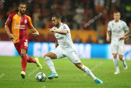 Real Madrid's Eden Hazard (R) in action against Galatasaray's Younes Belhanda (L) at UEFA Champions League group A match between Galatasaray and Real Madrid in Istanbul, Turkey 22 October 2019.