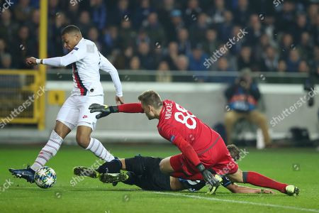 Stock Photo of PSG's Kylian Mbappe, left, shoots on goal as Brugge goalkeeper Simon Mignolet attempts a save during a Champions League Group A soccer match between Club Brugge and Paris Saint Germain at the Jan Breydel stadium in Bruges, Belgium