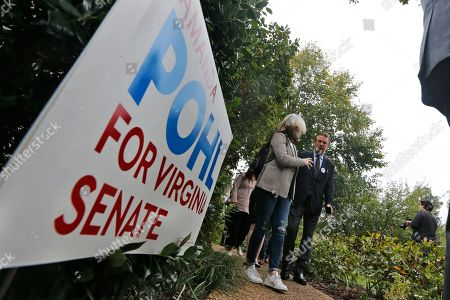 Actor Alec Baldwin, right, walks with a supporter of Amanda Pohl, candidate for Virginia Senate District 11 in her neighborhood in Midlothian, Va., . Baldwin campaigned for several candidates around the state