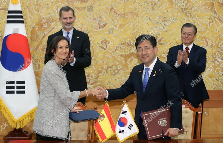 Stock Photo of King Felipe VI of Spain (L,back) and South Korean President Moon Jaei-in (R) applaud as South Korean Culture Minister Park Yang-woo (C-R) and Spanish Tourism Minister Reyes Maroto (C-L) shake hands after signing an agreement on bilateral trade cooperation at the presidential office in Seoul, South Korea, 23 October 2019.