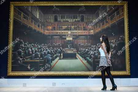"A staff member next to ""Devolved Parliament"", 2009, by Bansky (Est. GBP1.5-2m). Preview of Sotheby's Frieze Week Contemporary Art exhibition at its New Bond Street galleries. Over 250 works by artists, including Andy Warhol, David Hockney and Jean-Michel Basquiat, will be auctioned on 3 October 2019."