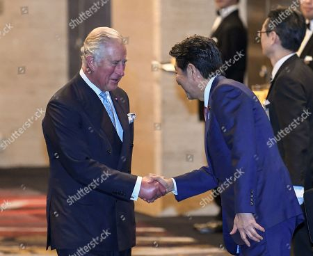 Prince Charles (L) shake hands with Prime Minister of Japan Shinzo Abe (R) at the cocktail party before a banquet for newly enthroned Emperor Naruhito, hosted by Japan's Prime Minister and his wife, at a hotel in Tokyo, Japan, 23 October 2019.
