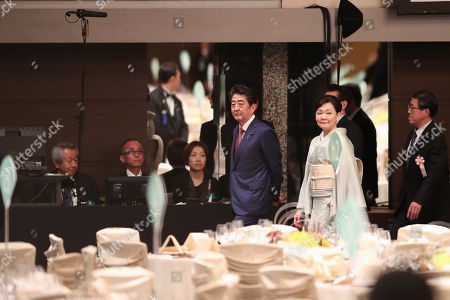 Stock Photo of Japan's Prime Minister Shinzo Abe, front left, and his wife Akie check the preparation situation at the banquet room before a banquet hosted by Abe in Tokyo