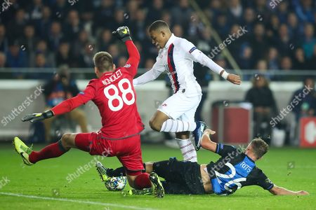 PSG's Kylian Mbappe, center, shoots the ball to score past Brugge's Mats Rits, right, and Brugge goalkeeper Simon Mignolet, left, during a Champions League Group A soccer match between Club Brugge and Paris Saint Germain at the Jan Breydel stadium in Bruges, Belgium