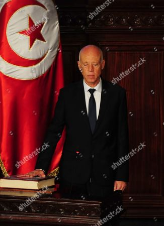 Newly elected Tunisian President Kais Saied puts his hand on the Quran to be sworn in as Tunisian President, in Tunis, Wednesday Oct.23, 2019. Tunisians elected former law professor Kais Saied as president earlier this month to replace President Beji Caid Essebsi, who died in July