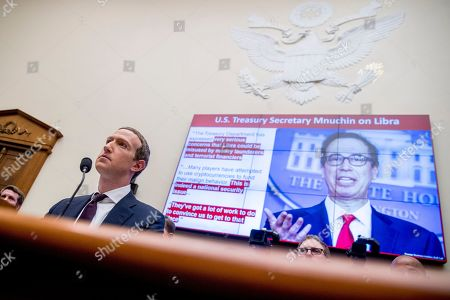 Comments from Treasury Secretary Steven Mnuchin on Facebooks Libra proposal are displayed on a monitor behind Facebook CEO Mark Zuckerberg as he testifies before a House Financial Services Committee hearing on Capitol Hill in Washington, on Facebook's impact on the financial services and housing sectors