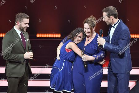 Actor Edin Hazanowic, Diala from Syria and her friend Laureate Jacqueline Flory and TV-Presenter Kai Pflaume during the 'Goldene Bild der Frau' ('Golden picture of the woman') awarding ceremony in Hamburg, northern Germany, 23 October 2019. The 'Goldene Bild der Frau' is awarded to women in voluntary positions.