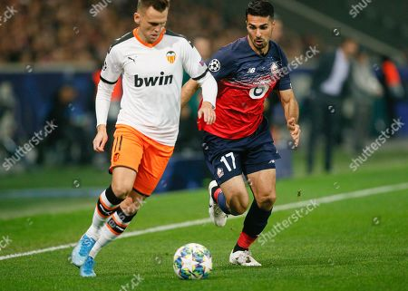 Valencia's Denis Cheryshev, left, challenges for the ball with Lille's Zeki Celik during the group H Champions League soccer match between Lille and Valencia at the Stade Pierre Mauroy - Villeneuve d'Ascq stadium in Lille, France