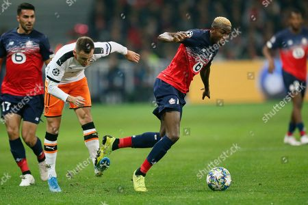 Lille's Victor Osimhen, right, is tackled by Valencia's Denis Cheryshev during the group H Champions League soccer match between Lille and Valencia at the Stade Pierre Mauroy - Villeneuve d'Ascq stadium in Lille, France