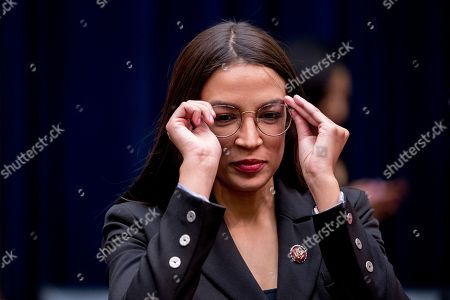 Rep. Alexandria Ocasio-Cortez, D-N.Y., speaks with other lawmakers during a break from testimony from Facebook CEO Mark Zuckerberg before a House Financial Services Committee hearing on Capitol Hill in Washington, on Facebook's impact on the financial services and housing sectors