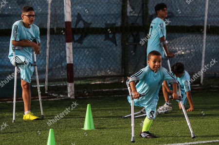 Palestinian amputees exercise during a soccer training session conducted by Irish coach Simon Baker