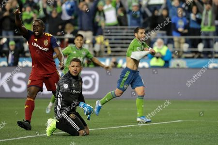 Real Salt Lake goalkeeper Nick Rimando, second from left, and defender Nedum Onuoha, left, react after Seattle Sounders forward Nicolas Lodeiro, right, scored a goal during the second half of an MLS Western Conference semifinal playoff soccer match, in Seattle. The Sounders won 2-0