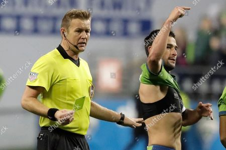 Referee Alan Kelly, left, gives a yellow card to Seattle Sounders forward Nicolas Lodeiro, right, for celebration after Lodeiro removed his jersey as he reacted to scoring a goal against Real Salt Lake during the second half of an MLS Western Conference semifinal playoff soccer match, in Seattle. The Sounders won 2-0