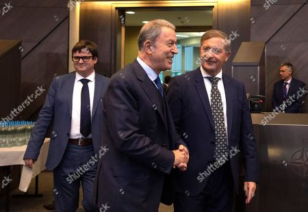 Turkish Defense Minister Hulusi Akar, left, speaks with Slovenian Defense Minister Karl Erjavec during a meeting of NATO defense ministers at NATO headquarters in Brussels, . NATO defense ministers gather for a two-day meeting to discuss the invasion of northern Syria by alliance member Turkey, amid deep concern over Ankara's actions