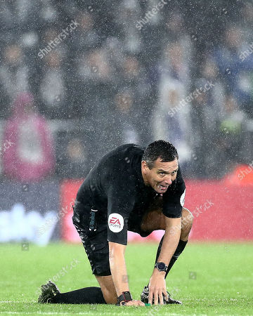 Referee Andre Marriner is seen on the ground after being struck by the ball.