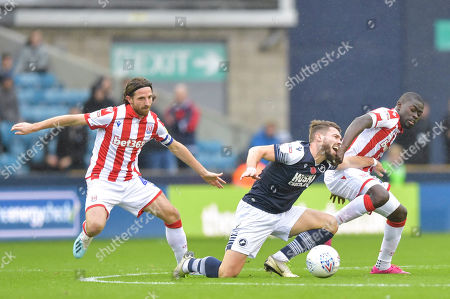 Tom Bradshaw of Millwall goes down under the challenge of Joe Allen of Stoke City and Badou Ndiaye of Stoke City