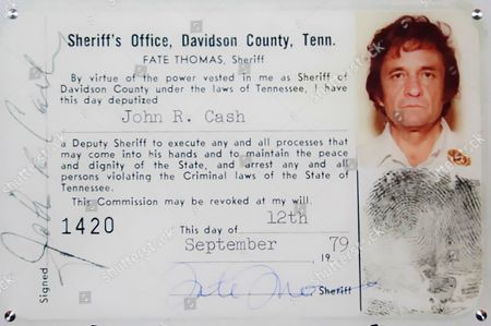 """This 1979 image released by the Davidson County (Tenn.) Sheriff's Office via the Johnny Cash Museum, shows Cash's Deputy Sheriff ID card. This week at the Johnny Cash Museum in Nashville, Tenn., Nashville Sheriff Daron Hall unveiled a blown-up image of the late musician's September 1979 deputy sheriff commission card. The card authorized Cash to """"execute any and all processes that may come into his hands and to maintain the peace and dignity of the State, and arrest any and all persons violating the Criminal laws of the State of Tennessee"""