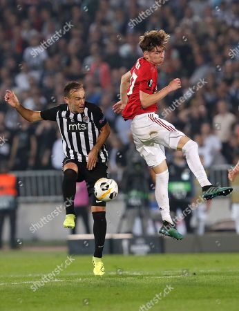 Manchester United's James Garner, right, jumps for a header with Partizan's Bibras Natkho during the Europa League group L soccer match between Partizan Belgrade and Manchester United at the Partizan stadium in Belgrade, Serbia