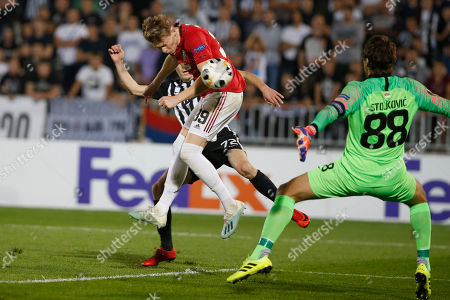 Manchester United's Scott McTominay, center, tries to score past Partizan's Slobodan Urosevic, back, and Partizan's goalkeeper Vladimir Stojkovic during their Europa League group L soccer match at the Partizan stadium in Belgrade, Serbia