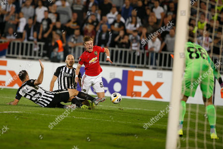 Manchester United's Brandon Williams, center, is fouled by Partizan's Bojan Ostojic, left, and Zoran Tosic, 2nd left, as Partizan's goalkeeper Vladimir Stojkovic follows the action during their Europa League group L soccer match at the Partizan stadium in Belgrade, Serbia